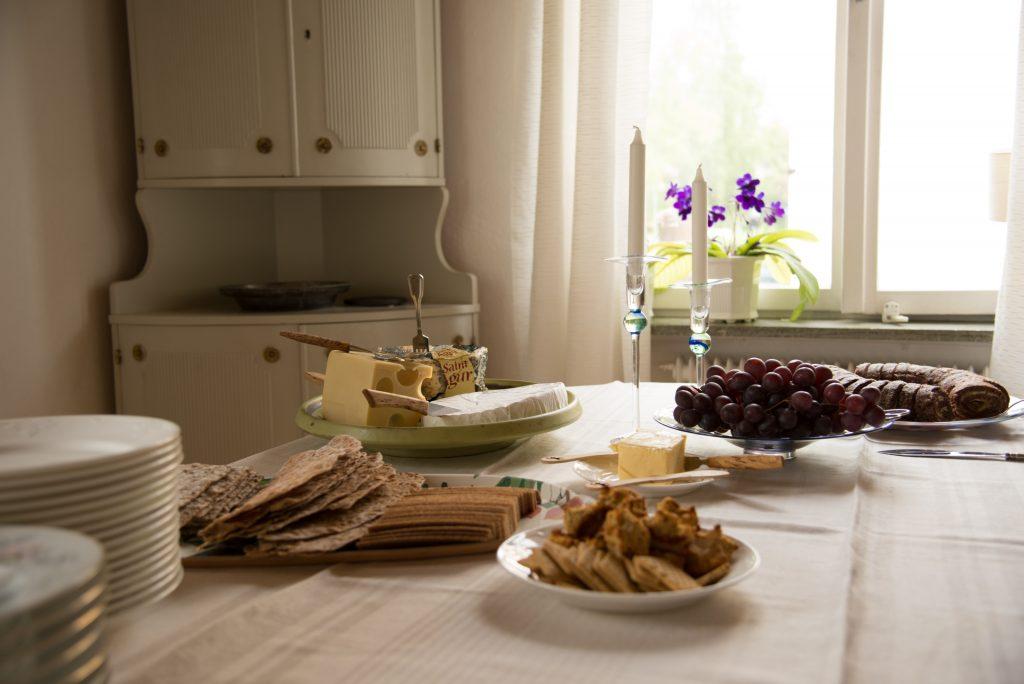 Un table dressée avec du fromage, des assiettes et du raisin